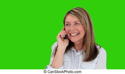 Retired woman laughing on the phone against a green screen