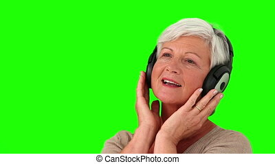 Retired woman listening to music with an headphones