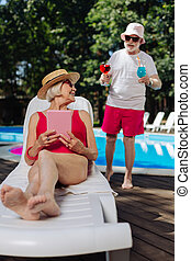 Retired woman lying on deck chair waiting for cocktails