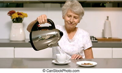 Retired woman pouring boiling water from kettle into cup in...