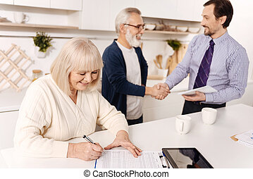 Retired woman signing contract while her husband greeting...