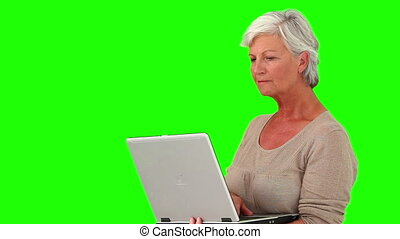 Retired woman standing with her laptop