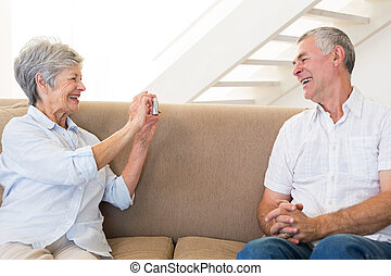 Retired woman taking photo of her partner on the couch