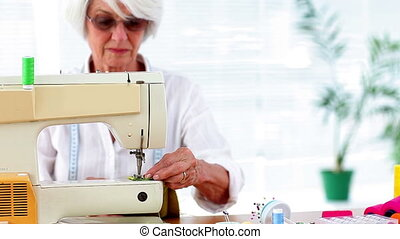 Retired woman using the sewing machine to make something at...