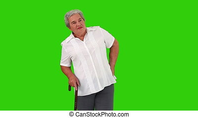 Retired woman with a stick having a back pain against a green screen