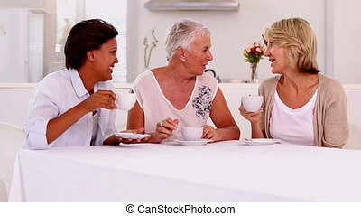 Retired women catching up over coffee at home in the kitchen