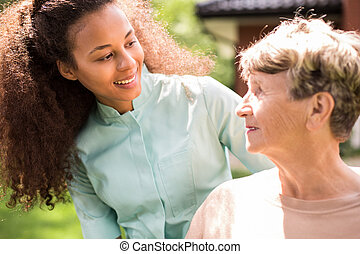 Portrait of retiree and African American nurse