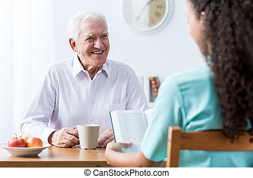 Retiree and nurse reading book at the table