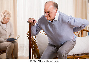 Retiree having backache - Retired man using walking stick...