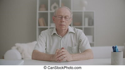 retiree man is greeting and talking distantly by online chat, medium portrait at living room, communicating by internet, part of video calling