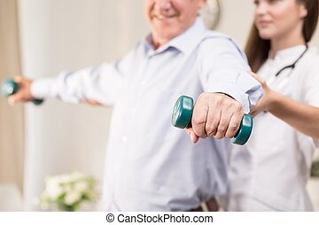Retiree training with dumbbells assisted by young physiotherapist