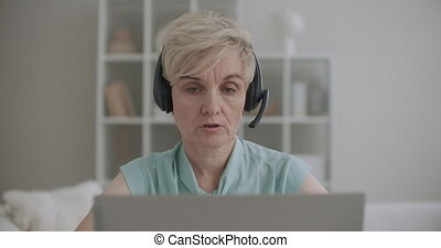 retiree woman is working from home in call-center, phone sales and tech support department, remote job, distant work for aged people, portrait of lady with laptop and headphones