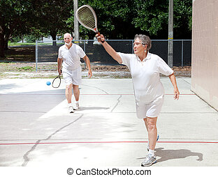 Retirees Playing Racquetball - Active senior couple playing...