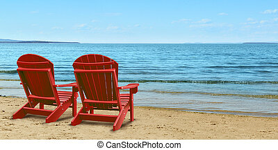Retirement Aspirations and financial planning symbol with two empty blue adirondack chairs sitting on a tropical sandy beach with ocean view as a business concept of future successful investment strategy.