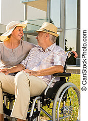 Retirement disabled man with wife outdoors