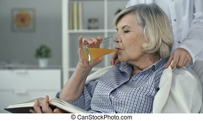 Close up of senior lady reading given juice to drink and smiling joyfully