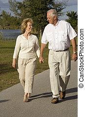 Retirement - Happy senior couple walking in a park