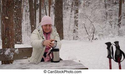 retraité, a, hiver, femme, thé, thermos., après, repos, banc, chaud, aller, wood., avoir, marche., assied, scandinave, personnes agées