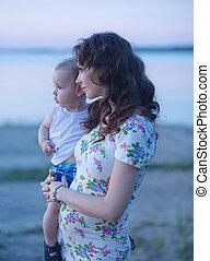 retrato, de, a, mãe feliz, segurando, dela, criança