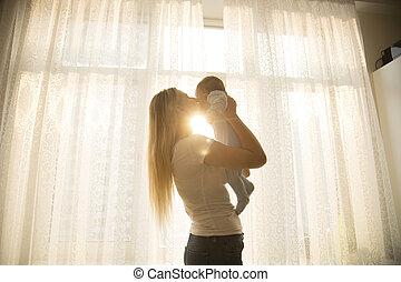 retrato, de, alegre, madre que celebra a su bebé, contra, grande, ventana