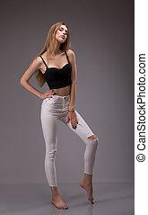 retrato, de, atraente, jovem, loiro, caucasiano, mulher, em, pretas, topo colheita, e, calças brancas, posing., tiro estúdio