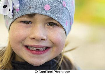 retrato, de, bonito, menina pequena sorrindo, com, um, caído, saída, leite, dente