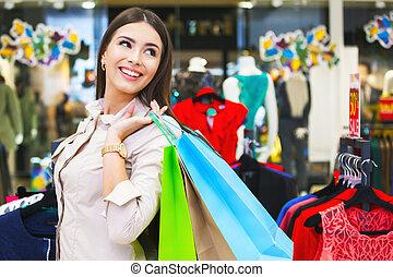 retrato, de, bonito, mulher jovem, com, bolsas para compras, em, roupa, store.