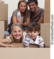 retrato, de, crianças, desembalando caixas, com, seu, pais