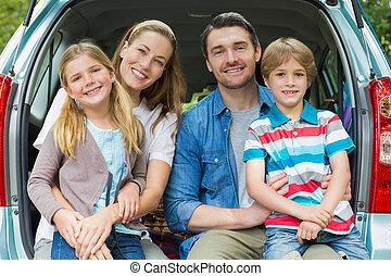 retrato, de, família feliz, de, quatro, sentando, carro, tronco