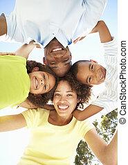 retrato, de, família feliz, olhando baixo, em, câmera, parque