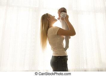 retrato, de, feliz, joven, madre, levantar arriba, ella, bebé, contra, ventana