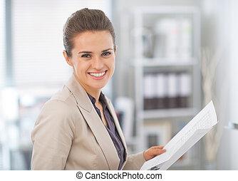 retrato, de, feliz, mujer de negocios, con, documentos, en, oficina