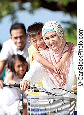 retrato, de, feliz, musulmán, familia , bicicletas de equitación, juntos
