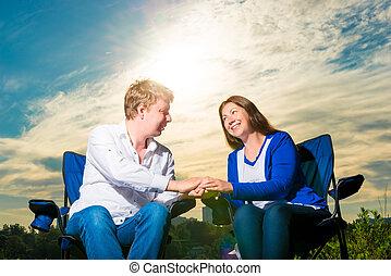 retrato, de, feliz, par cariñoso, en, salida del sol, en, sillas, aire libre