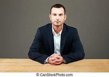 retrato, de, guapo, hombre de negocios, el sentarse en la tabla