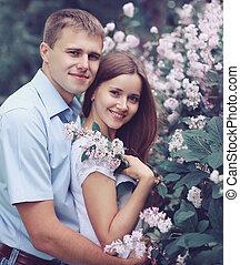 retrato, de, hermoso, pareja joven, en, el, florecimiento, primavera, jardín, dulce, amor