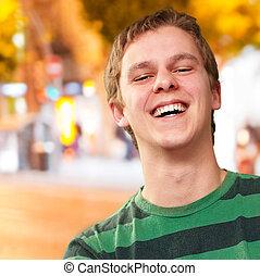 retrato, de, homem jovem, sorrindo, contra, um, noturna, cidade