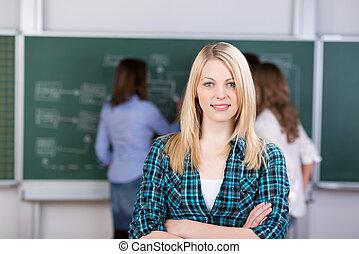 retrato, de, jovem, aluno feminino, sorrindo, com, professor, e, colegas, em, fundo