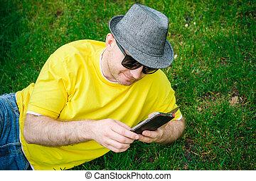 retrato, de, jovem, homem sorridente, em, chapéu, e, óculos, sentando, ligado, grama verde, com, telefone