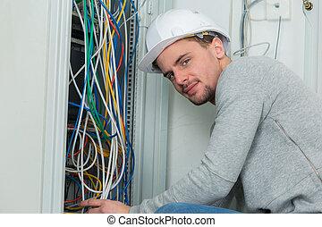 retrato, de, joven, electricista, cableado, un, eléctrico, panel
