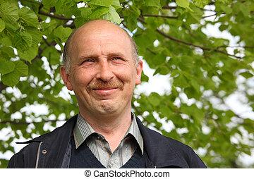 retrato, de, middle-aged, homem sorridente, ao ar livre