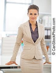 retrato, de, mujer de negocios, posición, en, oficina