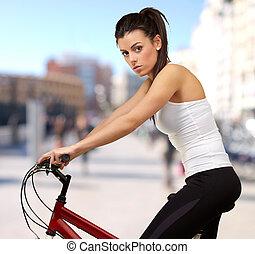 retrato, de, mulher jovem, ciclismo, em, cidade