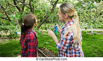 retrato, de, mulher jovem, com, filha, em, florescer, pomar