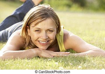 retrato, de, mulher jovem, relaxante, em, campo