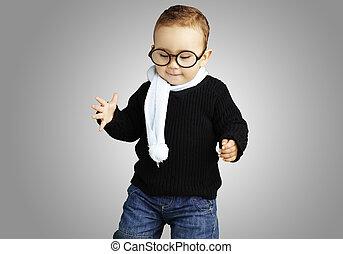 retrato, de, niño, llevando gafas, look down, contra, un, gris, espalda