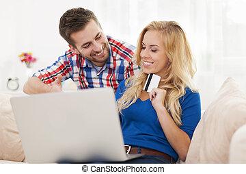 retrato, de, par, com, laptop, e, cartão crédito, em, sala de estar
