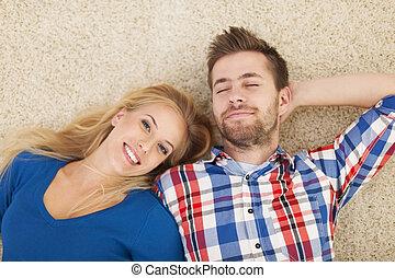 retrato, de, par jovem, deitando-se, ligado, tapete