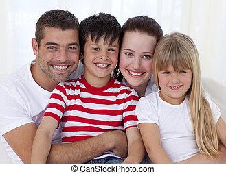 retrato, de, sonriente, familia , se sentar sobre sofá, juntos