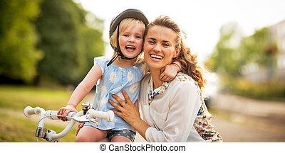 retrato, de, sonriente, madre y bebé, niña, sentado, en, bicicleta